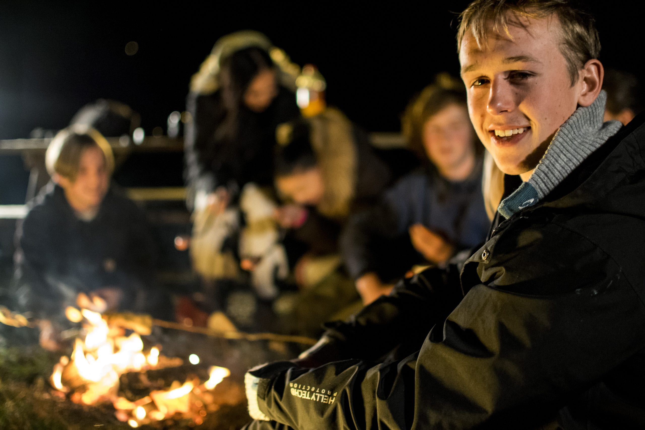 Ein kjekk gjeng som koser seg rundt leirbålet på kveldstid. Stord folkehøgskule.